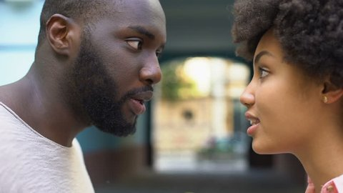 Young afro-american couple arguing outdoor, misunderstanding, jealous spouse