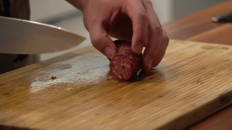cutting sausage on a cutting board in the kitchen.