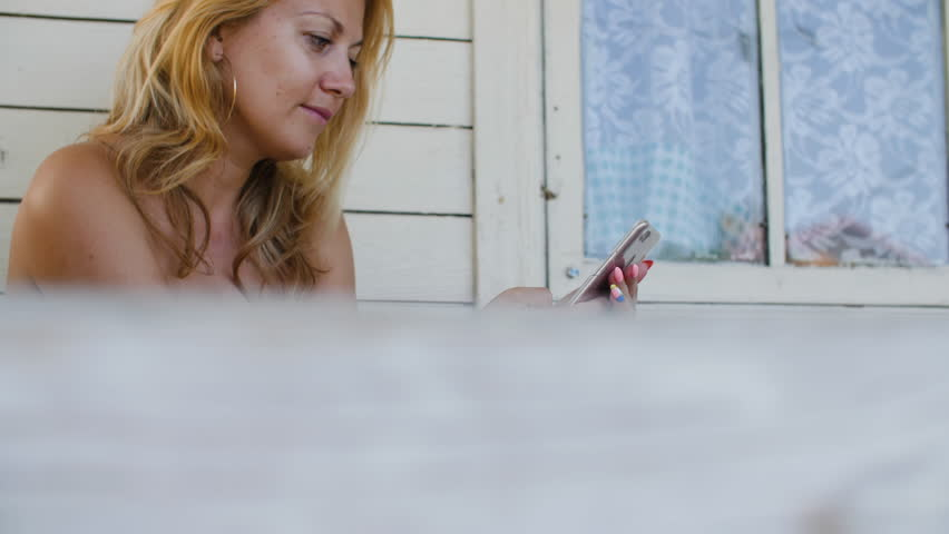 Adult woman using mobile phone while charging on outdoor terrace at summer house | Shutterstock HD Video #1013951987