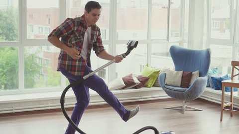 Man doing the cleaning vacuums and have fun dancing.Slow mo