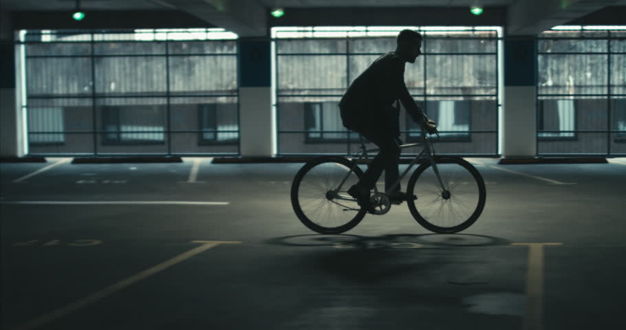 TRACKING Handsome young adult man wearing suit checking phone before riding his classic bicycle to work through an empty parking garage. 4K UHD 60 | Shutterstock HD Video #1013989817
