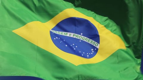 Brazilian national flag waving in wind front of blue sky. Flag of Brazil natural video.