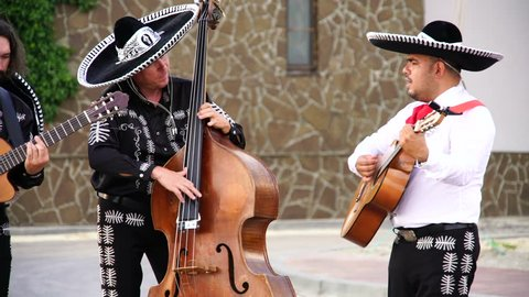 Mexican musicians mariachi play guitar outdoor. Musicians in traditional Mexican costumes and big hats at sunset.