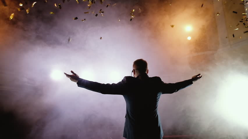 Successful businessman with arms up celebrating his victory. Celebrating success. Low angle view of excited young businessman keeping arms raised and expressing positivity while stands on the stage in | Shutterstock HD Video #1014025067
