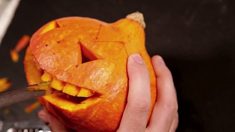 Footage of a person carving out the teeth of a Halloween pumpkin