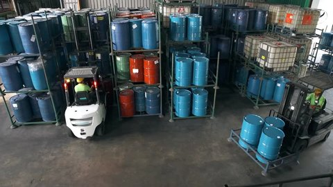 Fork-Lift Carrying 3 Barrels Passing Through Shelves Filled With Barrils