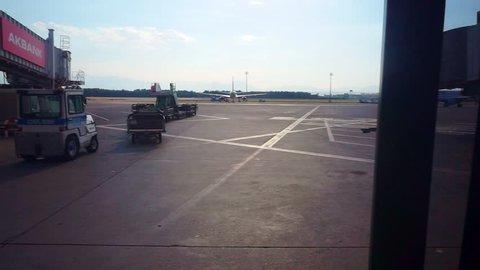 Antalya, Antalya / Turkey - July 14 2018: Antalya International Airport plane lands on the runway. footage filmed from the passenger terminal window