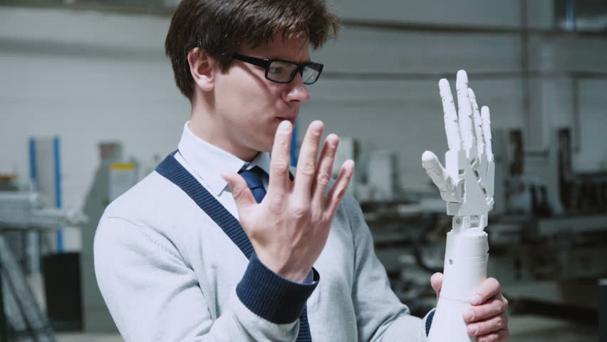 Robotic hand repeating the moves of young scientist's hand. Medacal hand prothesis 4K | Shutterstock HD Video #1014053717