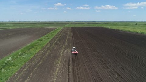 Farm machinery harvesting potatoes. Farmer field with a potato crop. Pile of potatoes on a trailer with vintage tractor. Aerial footage.