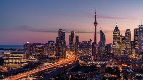 The historic Toronto Cn Tower in the midst of the entire downtown city skyline  with beautiful sunset with orange, red, and purple clouds along the horizon.