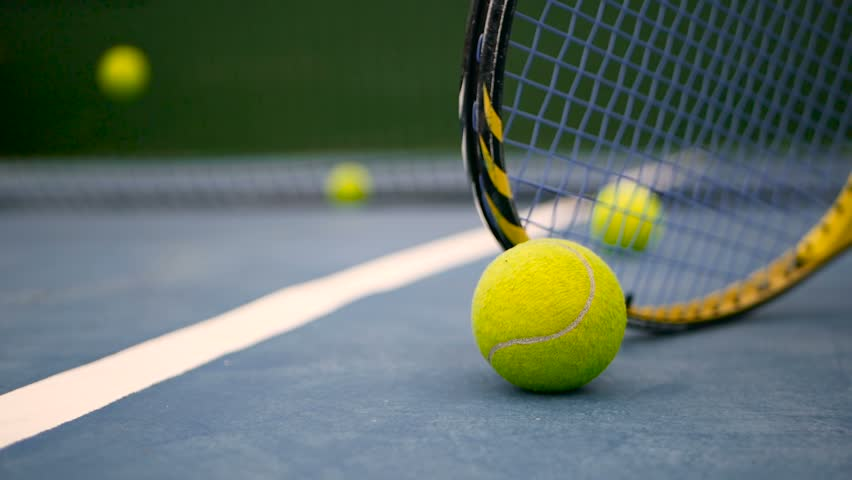 Close up of tennis equipment on the court. Sport, recreation concept. Yellow racket with a tennis ball in motion on a clay green blue court next to the white line with copy space and soft focus. #1014084767
