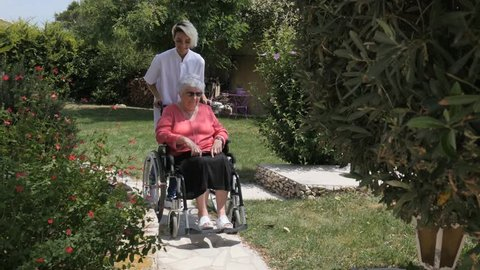 elderly senior woman on a wheelchair with nurse outdoor in nursing home hospital garden