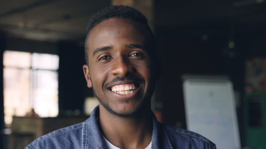 Close-up slow motion portrait of handsome African American man standing in loft style office, looking at camera and smiling. People, work and happiness concept. | Shutterstock HD Video #1014103487
