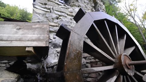 Old waterwheel mill. Water wheel. Water falls on an old water wheel. The old wooden mill wheel