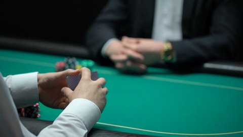 Male croupier shuffling and dealing cards at casino, player checking combination