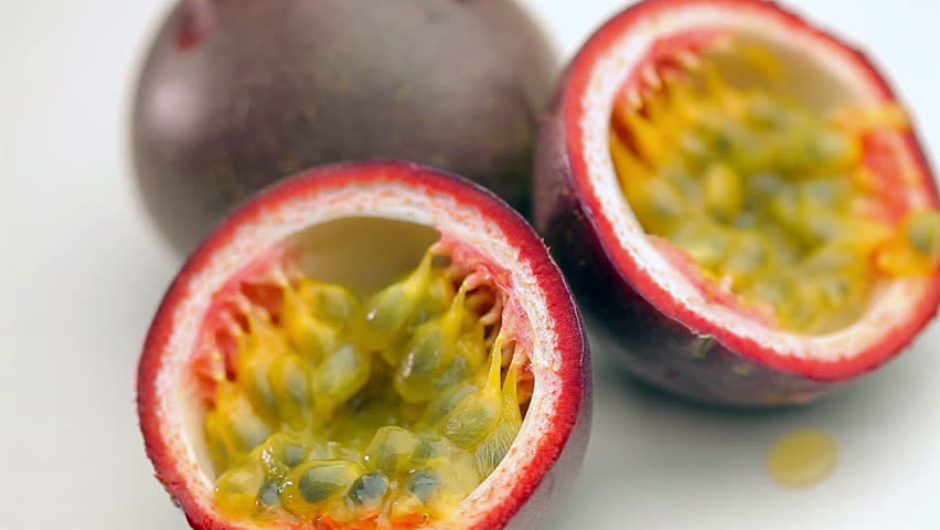 Halved Passion Fruit spin on white background.Close up footage of juicy exotic fruit.