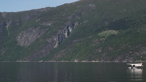 Small white floatplane getting ready for takeoff in Eidfjord, Norway.