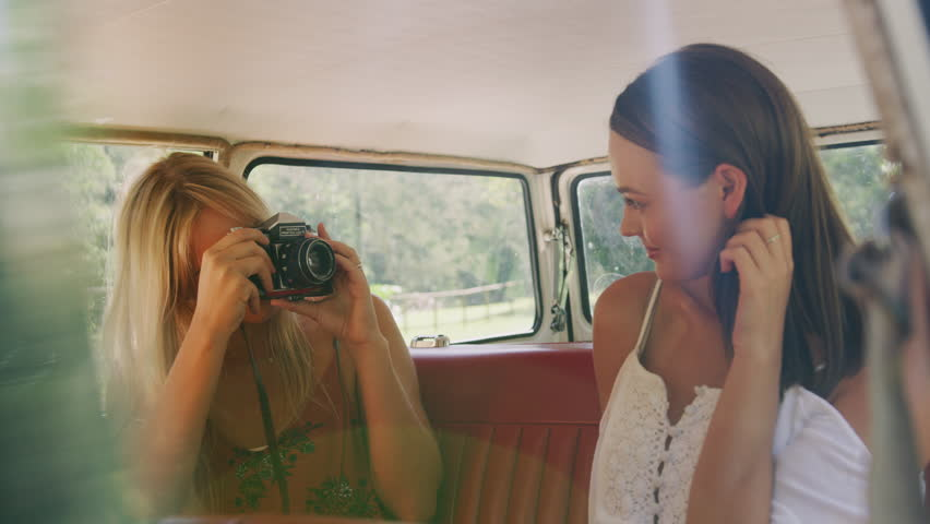 Two attractive girl friends having fun  taking pictures together at the back of a car. Shot with a RED camera. 4k footage.