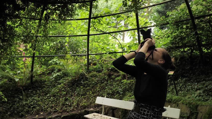 4k beautiful girl in black handmade dress standing inside of oval summer garden metal arbor construction shooting photo with dsl premium objetive in slow motion round moving motion camera #1014215507