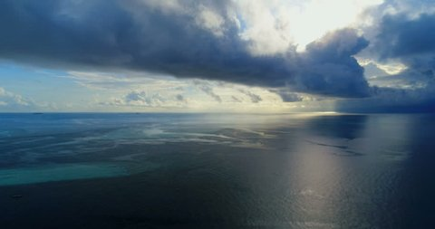 Aerial flying drone view of Maldives white sandy beach sunset sunrise on sunny tropical paradise island with aqua blue sky sea water ocean 4k