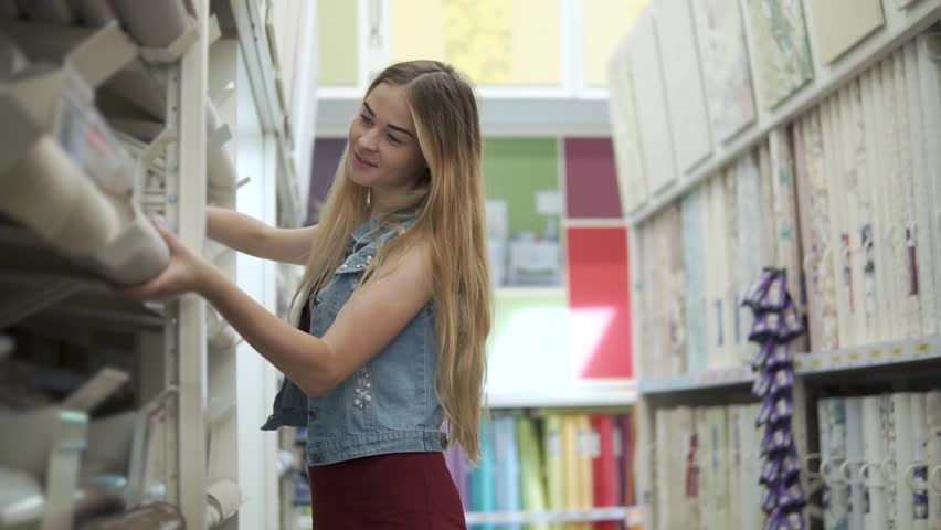 Charming young woman choosing new wallpaper for the room. Girl holding a roll of wallpaper with different patterns in hardware store.   Shutterstock HD Video #1014238427