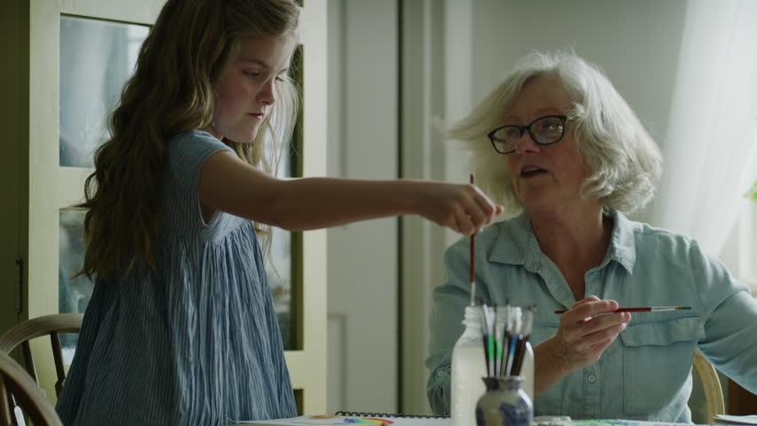 Grandmother teaching watercolor painting to granddaughter / Pleasant Grove, Utah, United States