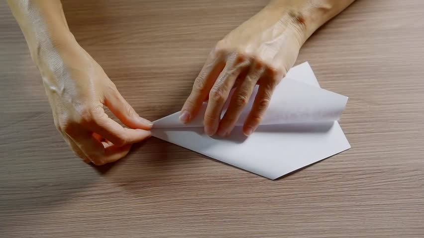 close up. woman hands folded model aircraft made of white paper on a table made of wood