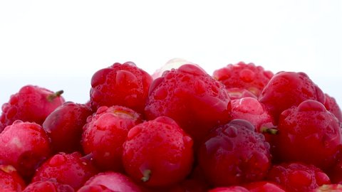 Pile of lingonberries rotating on the on the turntable isolated on the white background. Close up. Water drops.