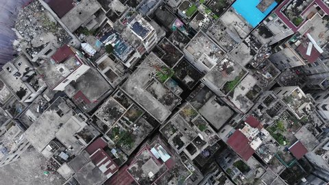 Empty old houses at urban slum area, prepared for demolition, top-down aerial shot. Old district of city will be cleared for new modern development. Camera fly down, show roofs of small housing units