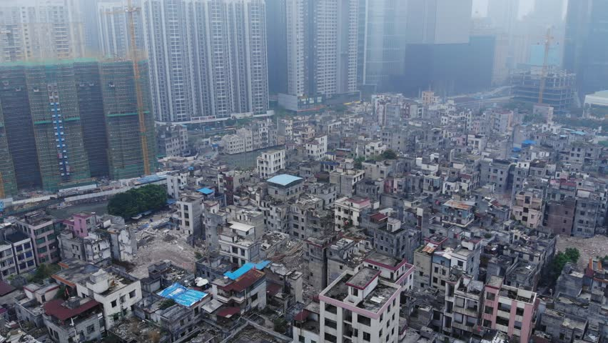 Abandoned slum area in middle of city, modern residential buildings seen ahead, aerial shot. Old part of city prepared for reconstruction, closely packed residential blocks, neglected buildings | Shutterstock HD Video #1014275087
