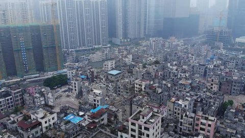 Abandoned slum area in middle of city, modern residential buildings seen ahead, aerial shot. Old part of city prepared for reconstruction, closely packed residential blocks, neglected buildings