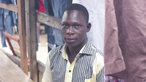 abidjan, Ivory Coast -July 17, 2018: Used clothes salesman sitting on a surprised bench, looking into the camera before lifting and showing his used clothes to his customers.
