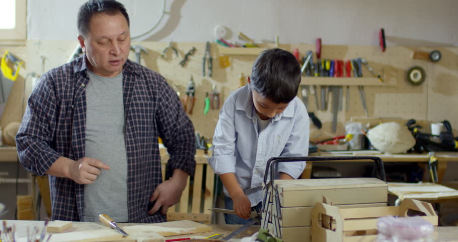 Medium shot of little Asian boy and his father working in carpentry workshop: they are looking at caliper device and taking measurements for next project