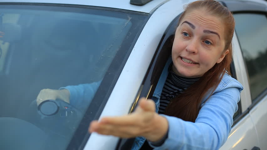 Middle aged woman sits in the car and complains on traffic situation - car stands on the verge of road in countryside | Shutterstock HD Video #1014362537