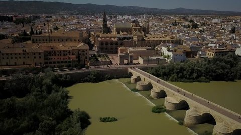 Aerial drone image of the medieval Spanish city of Cordoba, the Guadalquivir, the Roman Bridge and Tower and the Mezquita on a bright sunny day.  This is a famous tourist destination.