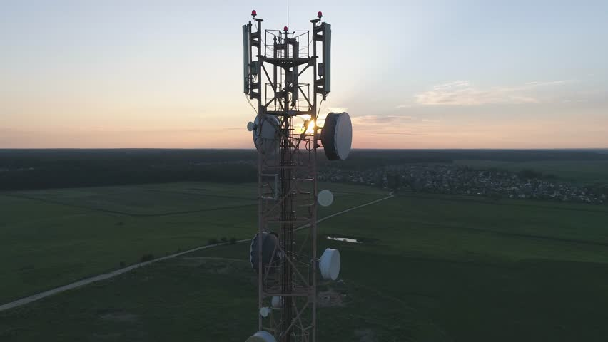 Aerial view of tower mobile station in sunlight, gsm antenna, view from height.    Shutterstock HD Video #1014385907