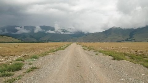 The steppe road goes to the mountains. Kurai steppe. altai republic. Cloudy weather.