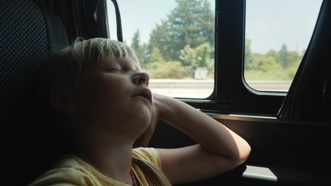 The girl is sleeping by the window in the back seat of the car. A Tedious Journey with a Child