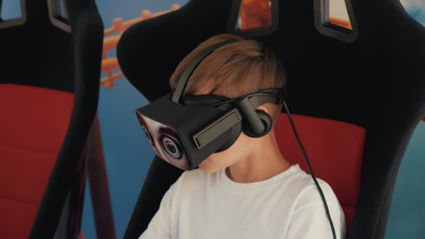 A boy in virtual reality glasses sits in an armchair on an attraction. The concept of the newest technologies | Shutterstock HD Video #1014407807