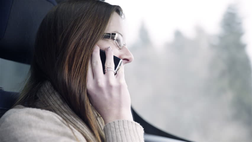 Talking on phone while driving in car 4K. Female person taking a call while driving car on road. Brown hair with glasses. Moving background. | Shutterstock HD Video #10144097