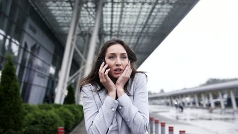 Close up view of Pretty Businesswoman Talking on Smartphone. Woman is in Hurry. Stressing and Busy Girl. Running Outdoor while Talking. Huge Glass Building in the Background.