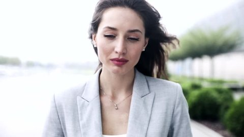 Close up view of Beautiful Young Woman Walking in the Street. Attractive Businesswoman in Despair. Looking Sad, Suppressed. Windy Weather. Pretty Girl Starting to Cry.