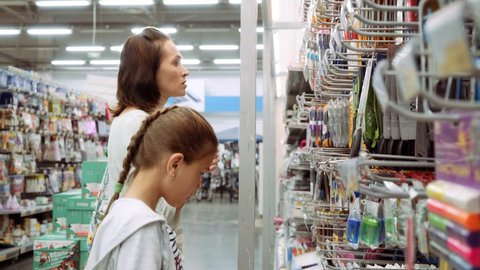 A woman with a daughter in a supermarket chooses stationery for school. Purchase of school supplies.