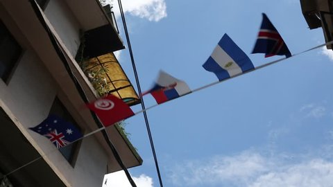 Serbian flag flying in the sky beside Tunisia flag and Argentina flag, 1080p 30ps