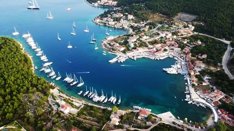Aerial video from iconic traditional fishing village and bay of Fiskardo with beautiful houses and Ionian architecture, Cefalonia island, Greece
