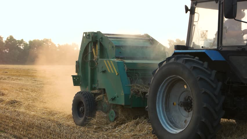 Farmer harvesting straw. Close up riding tractor on the field.