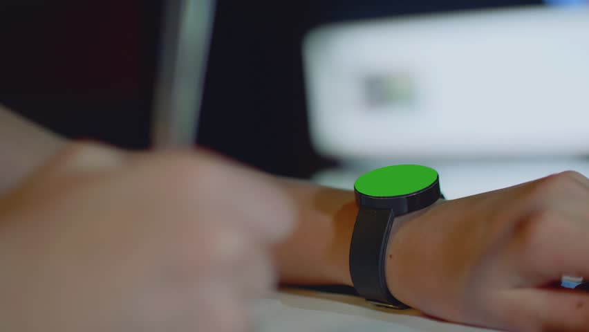 Focused balck watch with round green screen on girl's left hand and defocused pen in girl's right hand