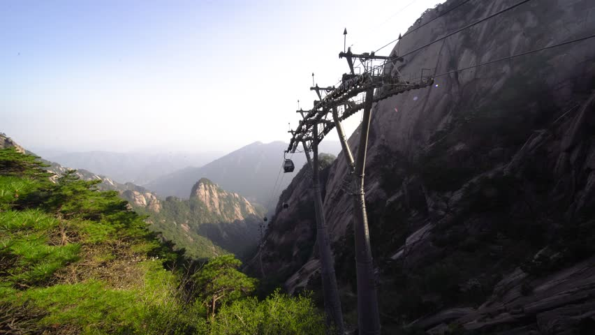 Cable car over Huangshan mountain in China. View of support pole of aerial tramway lifts tourists up mountainous area. Pylon holds up gondola lift in historic Chinese tourist site.