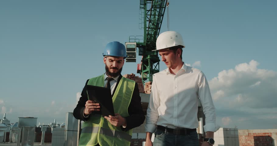 One businessman and young expert engineer analyzing on construction site the plan of a new building #1014527387