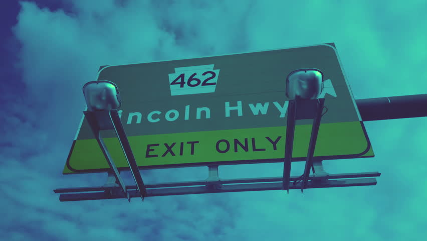 A low angle driver's view of passing under a Lincoln Highway PA Route 462 road sign.